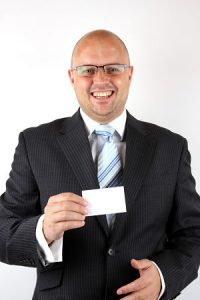 Smiling Businessman Holding a blank businesscard