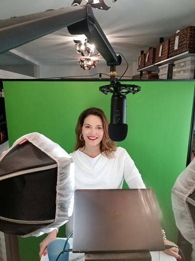 Virtual event auctioneer Sherry Truhlar in front of green screen at a virtual auction event