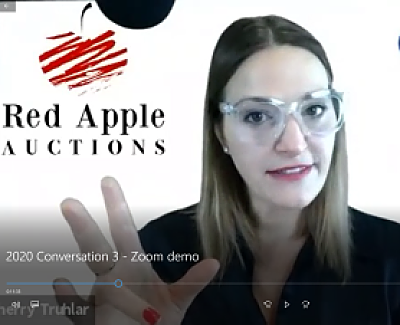 Screenshot of virtual gala auctioneer Sherry Truhlar in front of Red Apple Auctions' logo